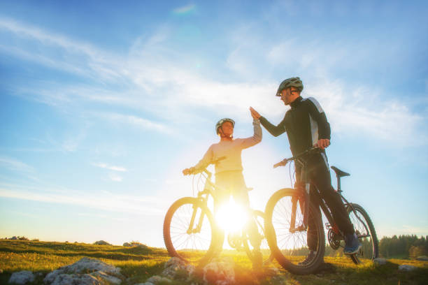 happy couple goes on a mountain road in the woods on bikes with helmets giving each other a high five happy couple goes on a mountain road in the woods on bikes with helmets giving each other a high five. female biker resting stock pictures, royalty-free photos & images