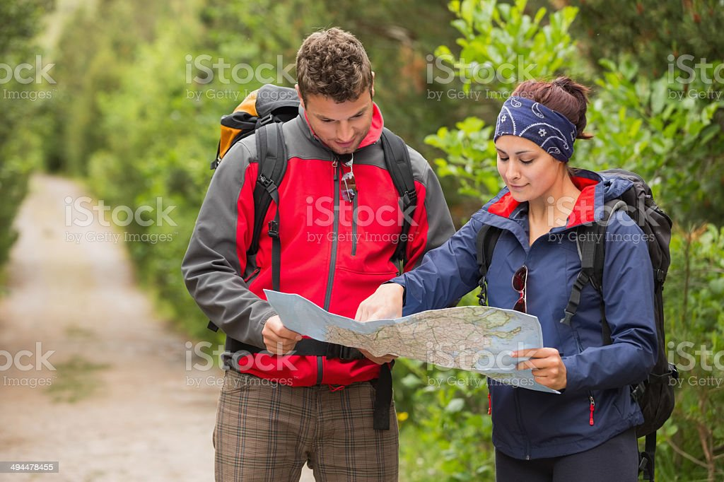 Happy couple going on hike together looking at map stock photo