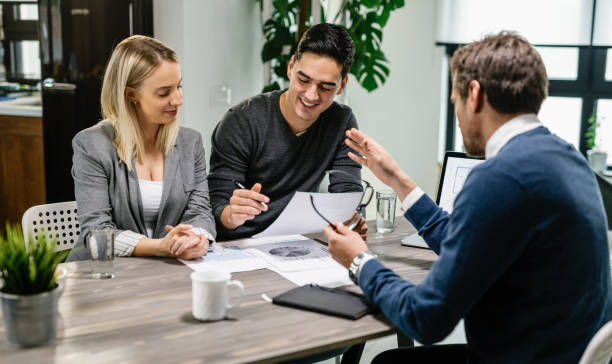Happy couple going through paperwork while having meeting with financial advisor. Young happy couple reading terms of mortgage documents while having meeting with real estate agent at home. Focus is on young man. mortgages and loans stock pictures, royalty-free photos & images