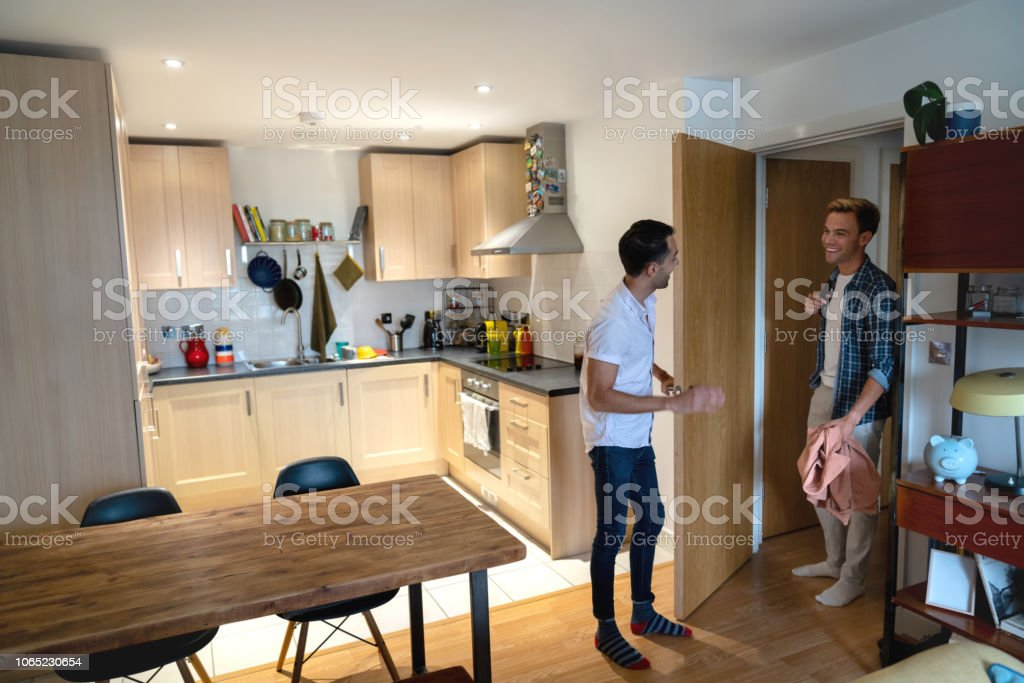 Happy couple greeting at the door at home Happy gay couple greeting at the door at home and smiling - lifestyle concepts 30-39 Years Stock Photo