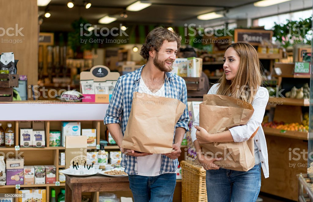 Happy couple grocery shopping stock photo