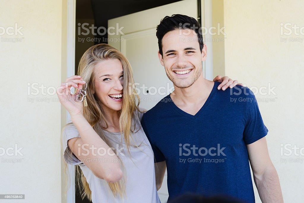 happy couple handing home keys in front of house door stock photo