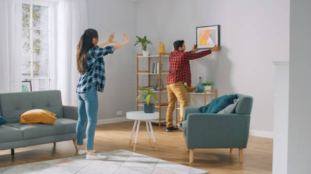 happy couple hanging picture on the wall, boyfriend moves it, girlfriend tells him when the frame is hanging straight. funny moment in young couple's life. modern stylish apartment. - украшать стоковые фото и изображения