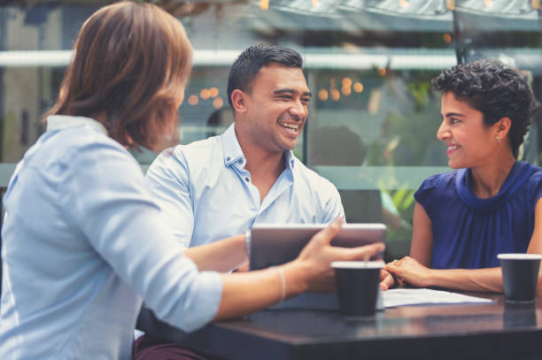 Happy couple having a business meeting with a financial advisor. stock photo