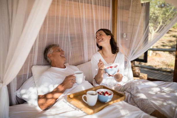 brautpaar mit frühstück im bett mit baldachin - bett landhausstil stock-fotos und bilder