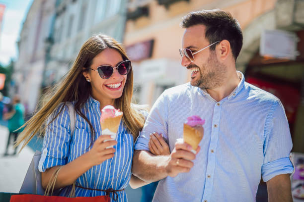 Pareja feliz teniendo fecha y comiendo helado después de ir de compras - foto de stock
