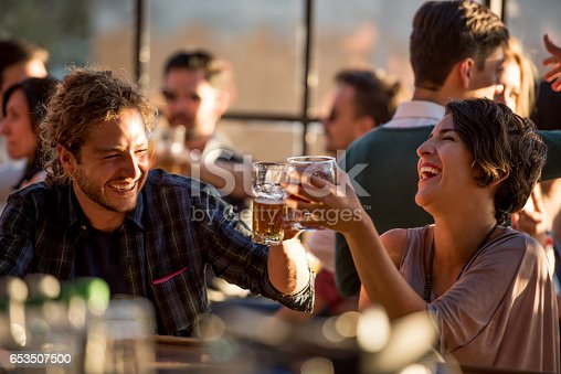 Happy couple having drinks at a bar and making a toast while having a lot of fun