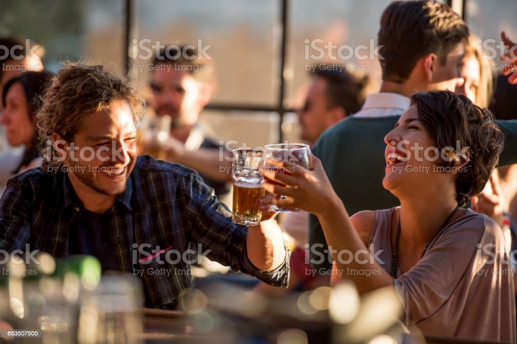 Happy couple having drinks at a bar stock photo