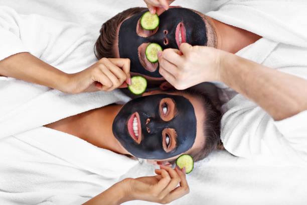 Glückliches Paar mit Gesichtsbehandlung im Spa-Salon – Foto