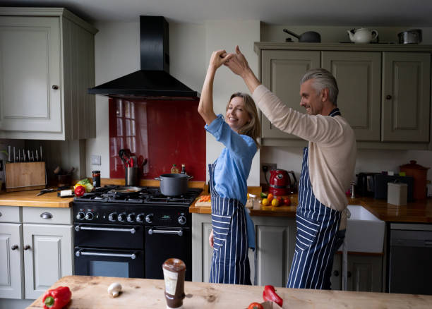 happy couple having fun dancing while cooking together - date night stock pictures, royalty-free photos & images