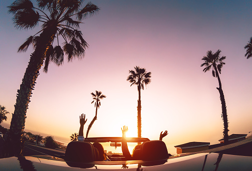 Happy couple having fun during road trip in convertible car - Young lovers enjoying vacation in tropical city - Love relationship and travel people lifestyle concept