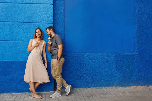 Happy couple having fun, eating ice cream and smiling against the blue wall stock photo