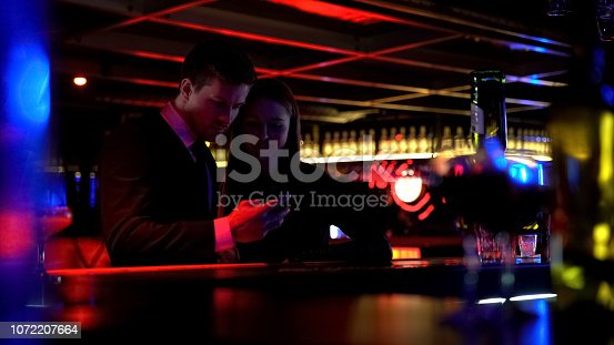 1072207668istockphoto Happy couple having fun in bar together, youth entertainment, night life 1072207664