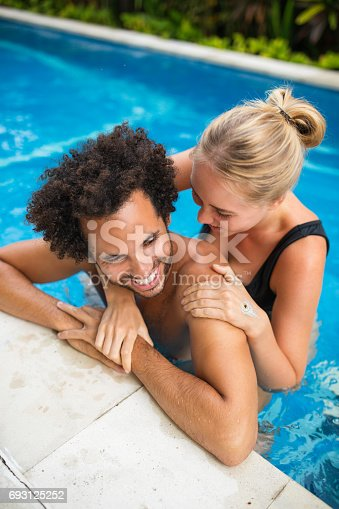 1065243116 istock photo Happy Couple Having Fun in Outdoor Swimming Pool 693125252