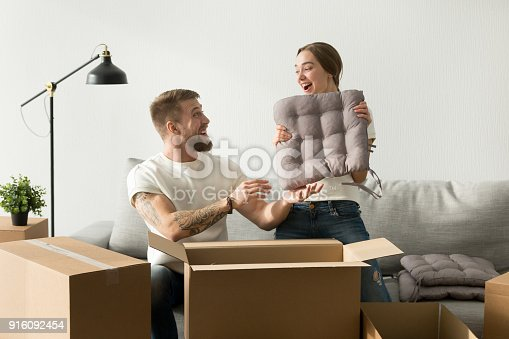 istock Happy couple having fun packing unpacking boxes in living room 916092454