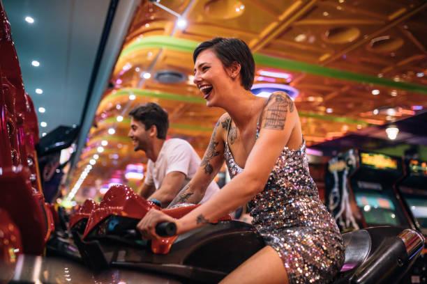 glückliche paare, die spaß spielen arcade racing spiele - arkade stock-fotos und bilder