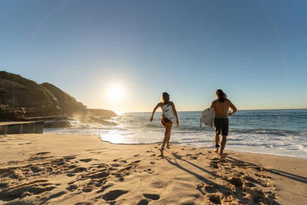 Glückliche Paare, die Spaß am Strand Surfen – Foto