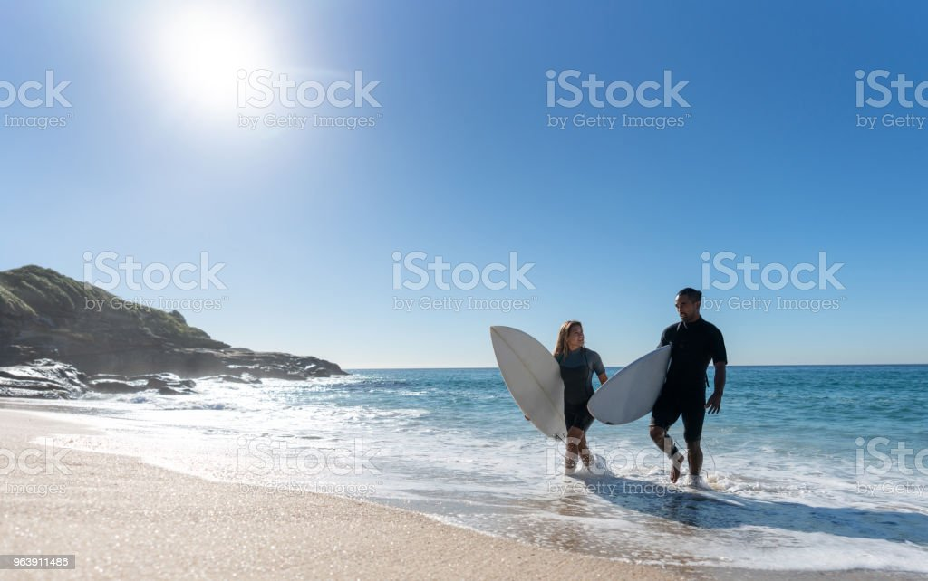 Happy couple having fun surfing at the beach - Royalty-free Adult Stock Photo