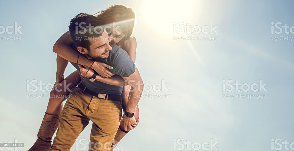 Happy couple having fun while piggybacking against the sky. royalty-free stock photo