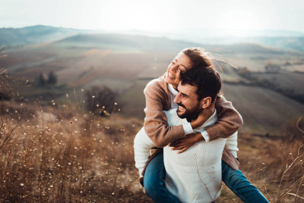 Happy couple having fun while piggybacking in autumn day outdoors. Young happy couple having fun while piggybacking on a hill. happy couple stock pictures, royalty-free photos & images