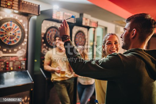 Young smiling couple having fun while playing darts with their friends in a bar. Focus is on man.