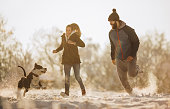 Playful couple having fun while running with Stafford dog on snow in the park. Copy space.