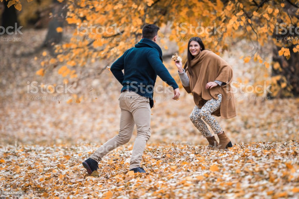 Happy couple having fun with autumn leaves in the forest. stock photo