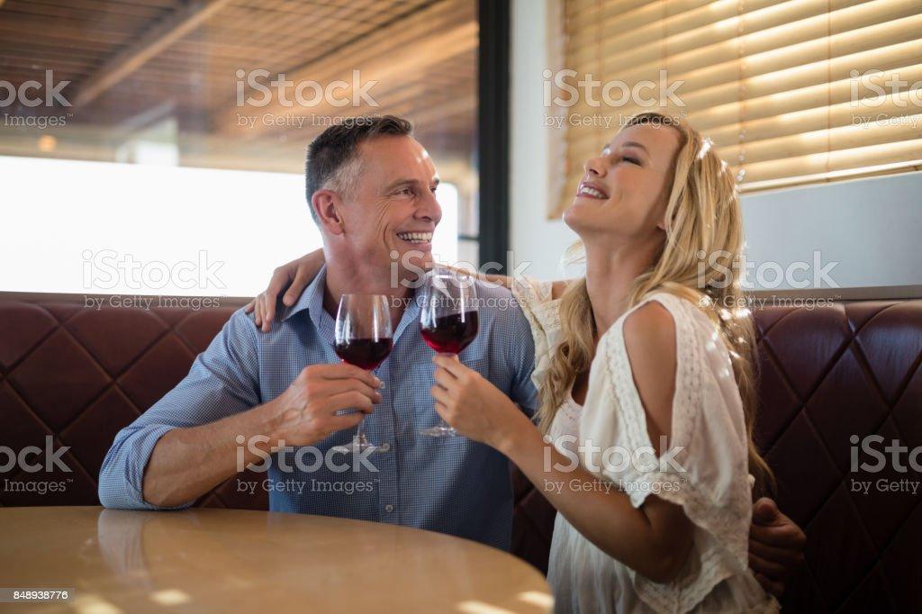 Happy couple having glass of wine stock photo