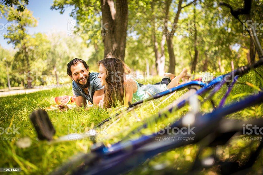 Glückliches Paar mit einem Picknick mit ihren bikes in den Vordergrund Lizenzfreies stock-foto