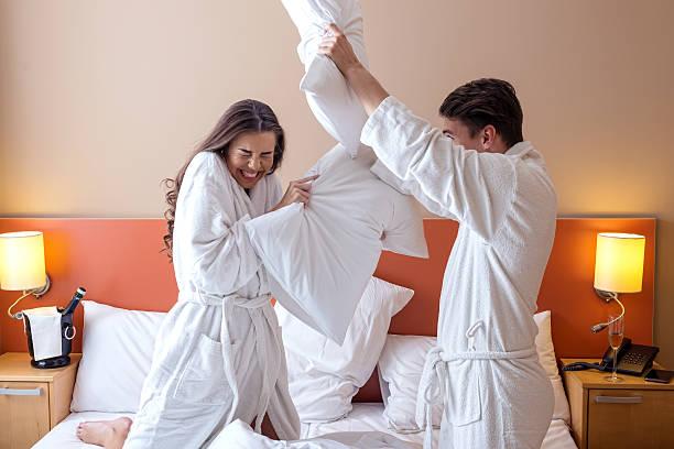 glückliches paar mit kissen kämpfen in hotelzimmer - kissenschlacht paar stock-fotos und bilder