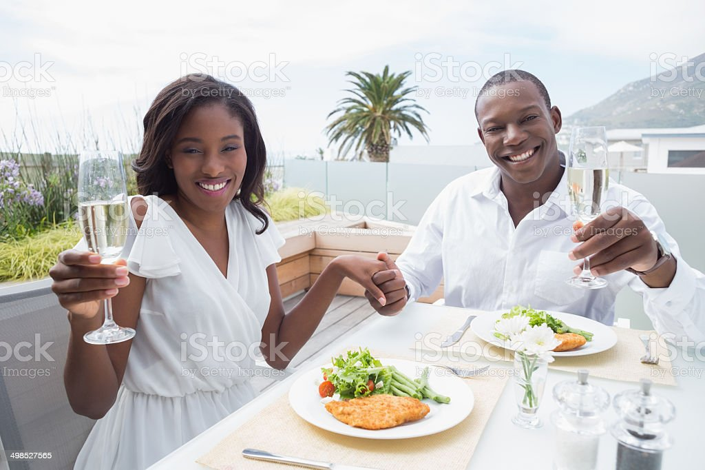 Happy couple having their lunch al fresco and drinking champagne royalty-free stock photo