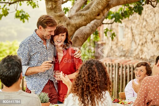 istock Happy couple having wine with family at lunch 800441784