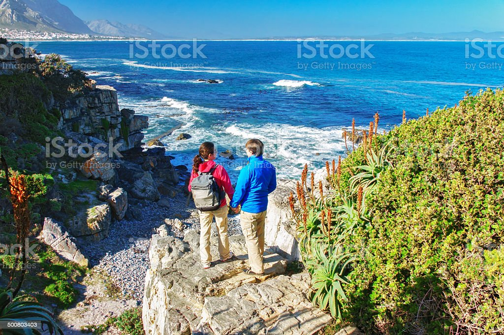 Happy couple hiking and looking at beautiful ocean view stock photo