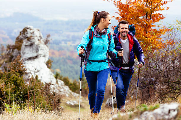 Happy couple hiking Woman and man hiking in mountains with backpacks nordic walking stock pictures, royalty-free photos & images