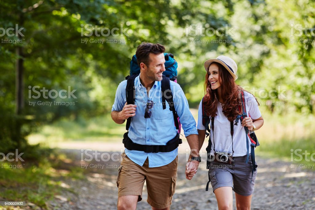 Happy couple hiking together in mountains with backpacks stock photo