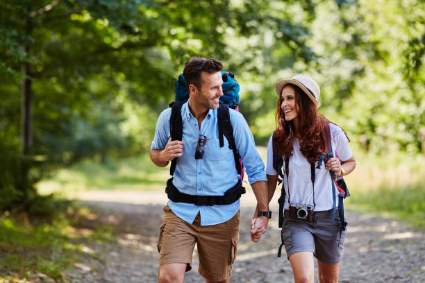 happy couple hiking together in mountains with backpacks - saccopelista foto e immagini stock