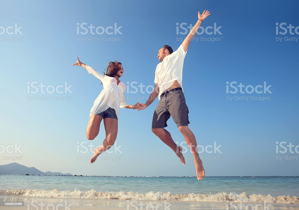 Happy couple holding hands and jumping on the beach. stock photo