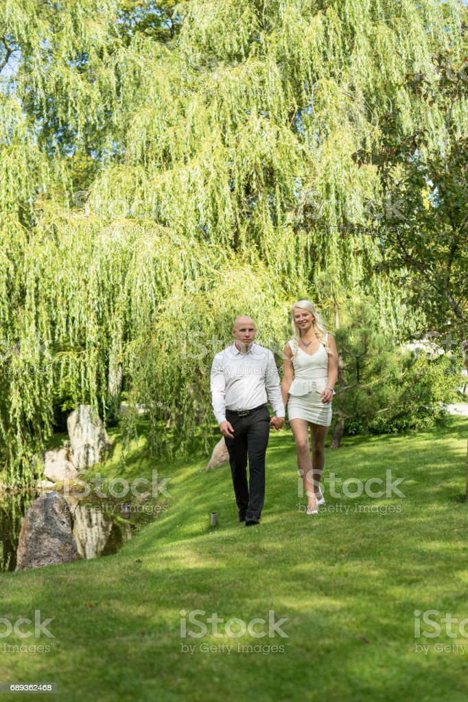 happy couple holding hands and walking in grass man and woman in