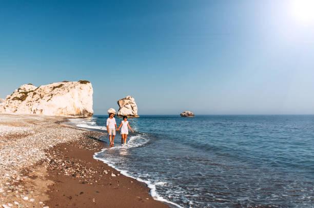 glückliches paar hält die hände zu fuß am sandstrand. paar verliebt bei sonnenuntergang am meer. paar verliebt im urlaub. reisemurlaubskonzept. romantisches ehepaar bei sonnenuntergang bei einem strandspaziergang - hochzeitsreise zypern stock-fotos und bilder