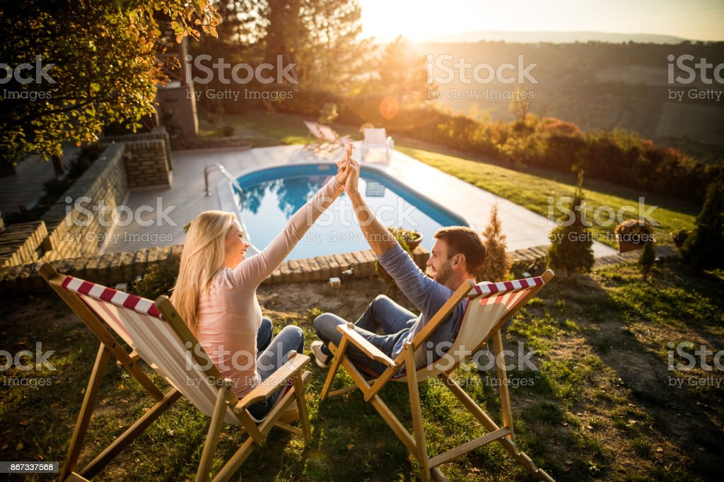 Happy couple holding hands while relaxing in deck chairs by the pool. stock photo