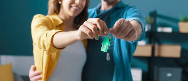 Happy couple holding house keys stock photo