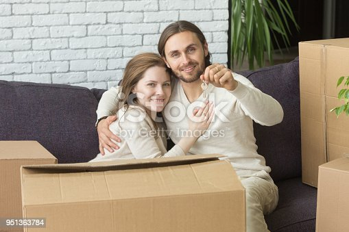 938682826istockphoto Happy couple holding keys looking at camera sitting on couch 951363784
