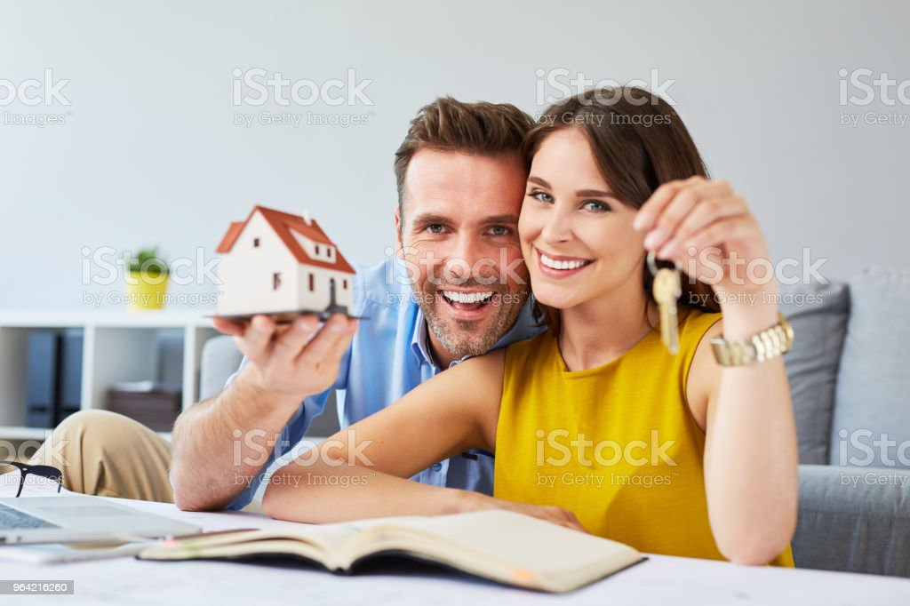 Happy couple holding keys to new home and house miniature stock photo