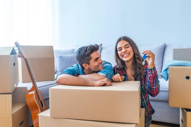 glückliches paar betrieb schlüssel in neues zuhause - eigenheim stock-fotos und bilder