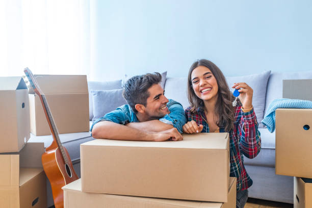 Happy couple holding keys to new home Cheerful and happy young couple holding the keys of their new home with moving cardbox during move into new apartment. Happy couple holding keys to new home. Couple celebrating moving to new home home ownership stock pictures, royalty-free photos & images