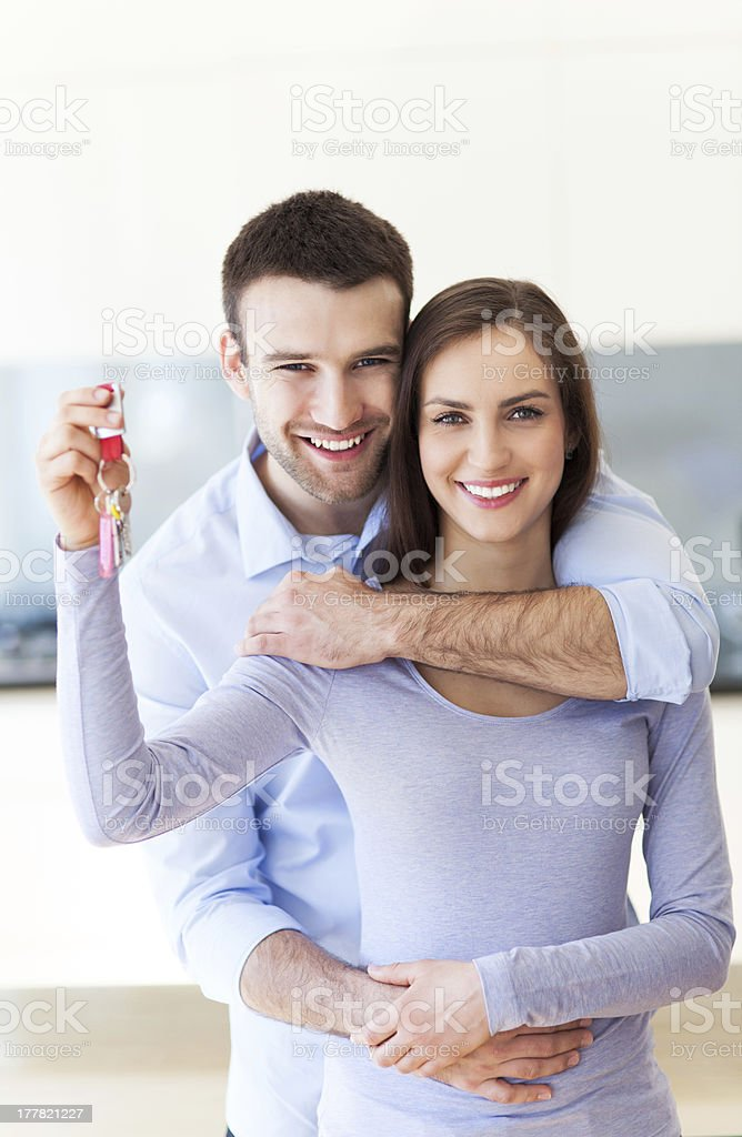 Happy couple holding keys to their new home stock photo