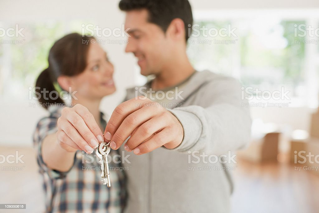 Happy couple holding keys to their new house royalty-free stock photo