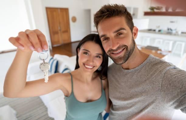 Glückliches Paar hält Schlüssel zu ihrem neuen Haus – Foto