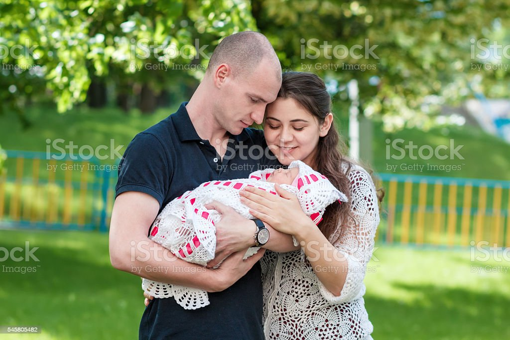 Happy couple holding their newborn daughter in her arms. Outdoors – Foto