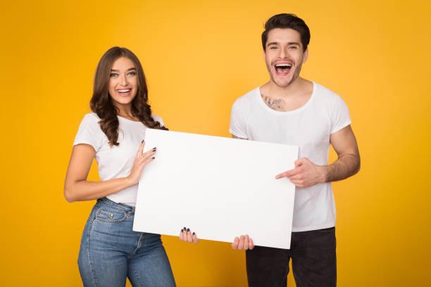 glückliches paar hält weißes banner mit kopierplatz - spaß sprüche stock-fotos und bilder
